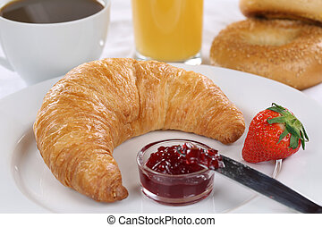 Breakfast with a croissant, coffee and orange juice