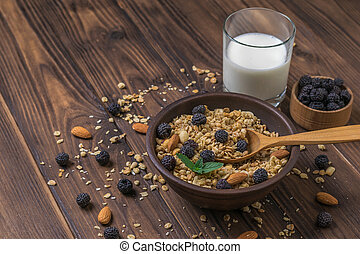 Breakfast with a glass of milk, granola and berries on a wooden table.