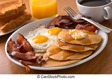 Breakfast with bacon, eggs, pancakes, and toast - A ...