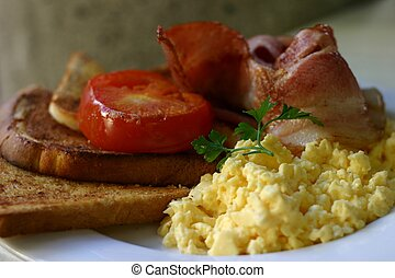 Breakfast with bacon, scrambled eggs, tomato and toast