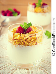 Breakfast with cereal flakes, yogurt and fresh raspberries