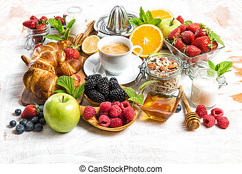 Breakfast with coffee, croissants, muesli, berries, fruits
