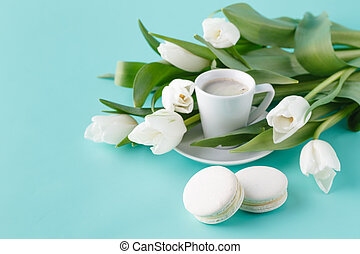 Breakfast with coffee cup and white tulips on plain background