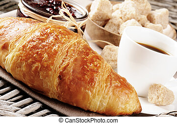 Breakfast with coffee, French croissant and jam on wicker tray