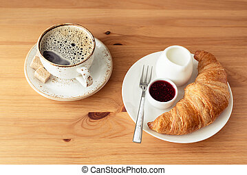 Breakfast with croissant, jam and coffee