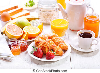 Breakfast with croissants, coffee, orange juice, toasts and fruits