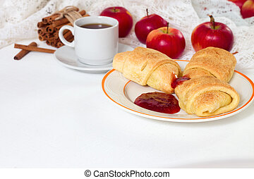 Breakfast with croissants, honey and apples and cup of espresso coffee on white rustic wooden background, top view.