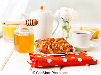 breakfast with croissants, honey and coffee