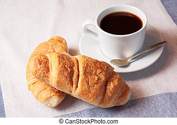 Breakfast with cup of black coffee and croissants