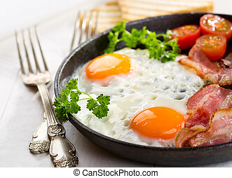 breakfast with fried eggs - pan of fried eggs, bacon and...
