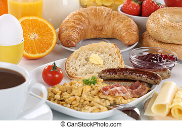 Breakfast with orange juice, marmalade, coffee, sausage, bagels, fruits and scrambled eggs