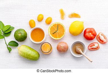 Breakfast with orange juice, oranges, oranges slice, passion fruit , ginger, tomato and Kiwi set up on wooden table .