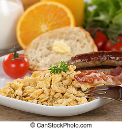 Breakfast with scrambled eggs, sausages and fruits