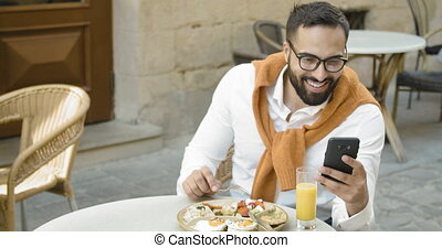 Attractive asian businessman using smartphone while having breakfast in outdoors cafe