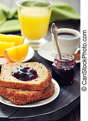 Breakfast with toast, fruit jam, juice and coffee on tray