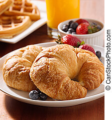 breakfast with two croissants and berries.