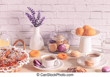 Breakfast with various macaroons, croissants and hot chocolate.