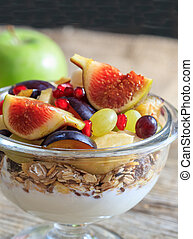 Breakfast with Yogurt, muesli and fresh fruits in a bowl, blur background
