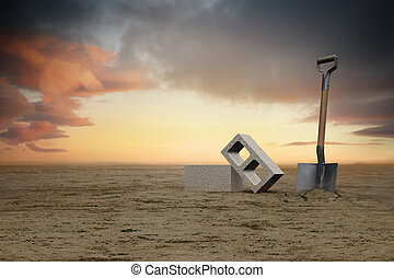 Image of two cement cinder blocks in the sand next to a shovel at sunset.