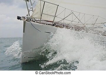 Close up on the bow of a sailing yacht breaking through a wave