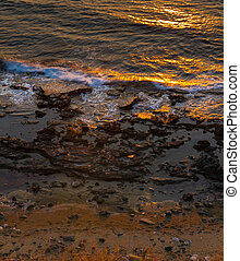 Breaking waves on rocky seashore and sun reflections at sunset