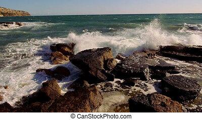 Breakings ocean waves hitting against a rocky coast