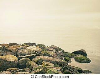 Breakwater in calm water of evening sea.
