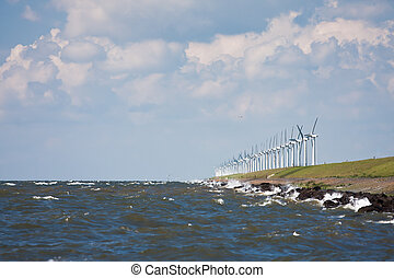 Breakwater with windmills during a heavy storm
