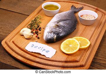 Bream fish on cutting board, ingredients, recipe label, ...