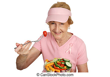 A senior woman in pink with Breast Cancer Awareness ribbon, eating healthy salad. Isolated on white.