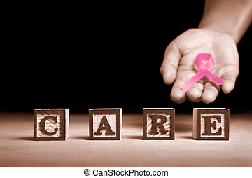 Word 'Care' from wooden block with hand holding pink ribbon on dark background