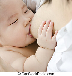 Asian mother breast feeding her infant