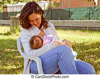 Breastfeeding - A pretty young brunette mum breastfeeding...