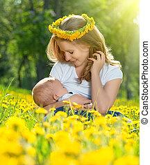 breastfeeding., mãe, alimentação, dela, bebê, em, natureza, prado verde, com, amarelo floresce