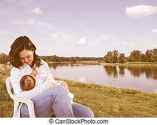 Pretty young brunette mum breastfeeding her baby in the country vintage