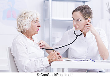 Breath in and breath out... - Doctor checking senior...