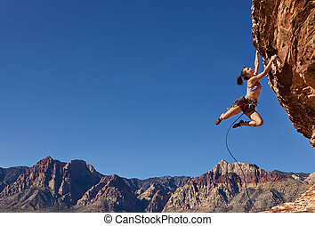 Female rock climber struggles for her next grip dangling midair on a challenging ascent.