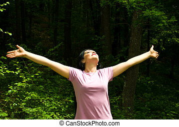 Breathing the fresh air from a spring forest - Young woman ...