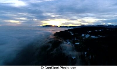 Breathtaking aerial 4k drone panorama flyover in dense heavy rain cloud fog sky in evening sunset mountain landscape
