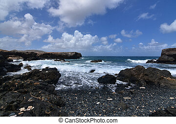 Beautiful look at the lava rock and horizon on Aruba's black sand stone beach.