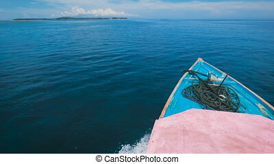 Breathtaking view of endless ocean in Bali and rostrum of the yacht sailing ahead. Incredible scene of the sea with the boat swimming. Indonesian marine landscape of turquoise water and blue sky.
