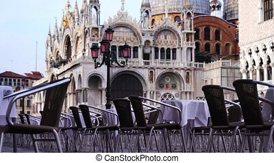 Breathtaking view on famous Saint Mark Basilica building ancient architecture behind outdoor cafe tables low angle shot