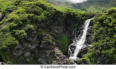 breathtaking waterfalls among large rocks with green trees -...