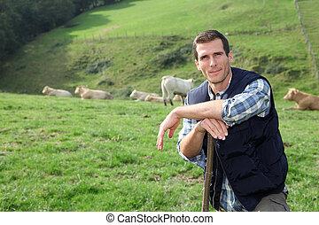 Breeder standing in pasture land