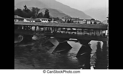 people walking on the historical old Alpini bridge of Bassano del Grappa town in Italy. Bridge was build in 1209, restored some times in years from architect Andrea Palladio. Historical 1960 footage.