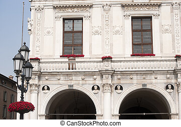 Brescia (Lombardy, Italy), Loggia Palace, historic building of Renaissance era with street light and red flowers