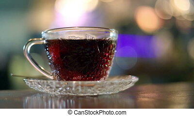 Brewing black tea with hot water in a glass cup