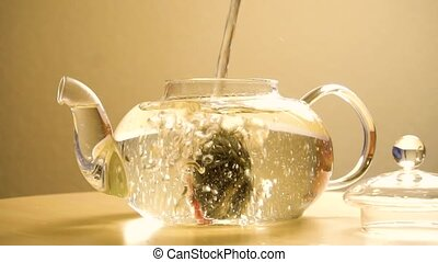 Brewing green tea in tea pot in slow motion