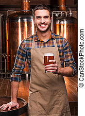 Brewing the best beer. Happy young male brewer in apron...