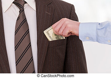 Bribing. Close-up of businessman putting money to the pocket of another man in formalwear